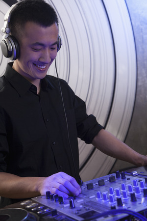 night club series: A portrait of a young male DJ playing music in a nightclub