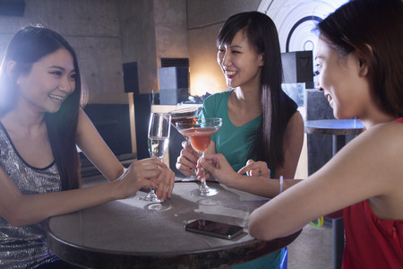 A group of young women having drinks in a nightclub photo