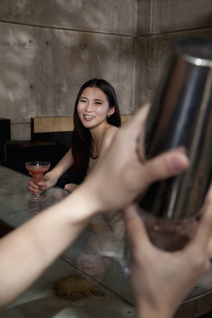 Young woman sitting at bar counter observing bartender photo