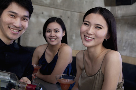 night club series: Portrait of young women and bartender at a bar Stock Photo