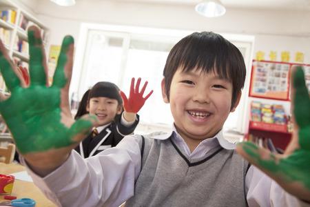 escuela primaria: Los escolares que muestran sus manos cubiertas de pintura