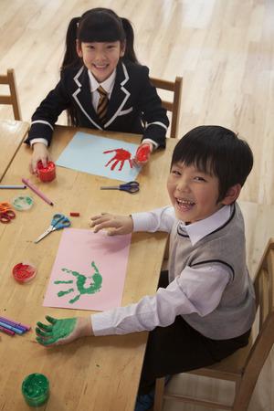 all under 18: School children finger painting in art class, Beijing