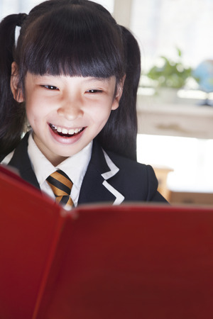 Schoolgirl reading a book with her face lit up  photo