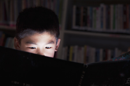 Close up of a schoolboy reading a book with his face lit up photo