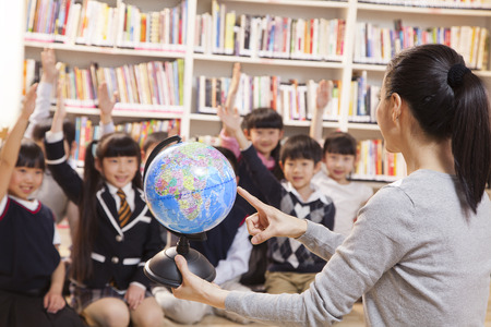 Teacher teaching geography to schoolchildren with a globe photo