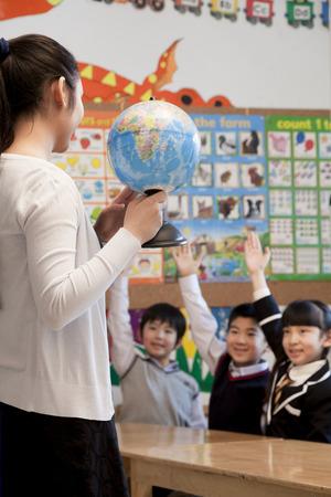 Teacher teaching geography to schoolchildren with a globe photo