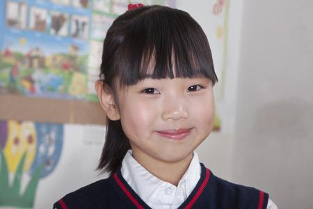 all under 18: Portrait of schoolgirl in classroom, Beijing, China