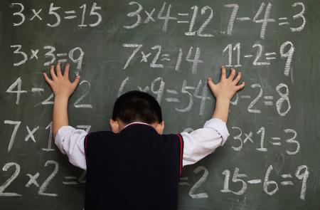 all under 18: Schoolboy in front of blackboard with hands on chalkboard