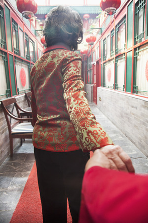 above 30: Senior couple holding hands, rear view Stock Photo