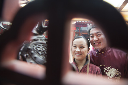 above 30: Couple holding offering incense at the temple in traditional clothing Stock Photo