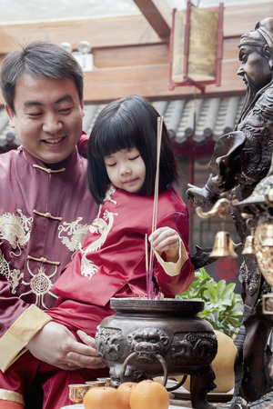 Father and daughter offering incense at the temple in Beijing photo