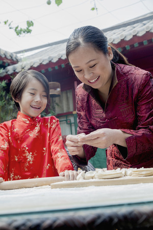 some under 18: Mother and daughter making dumplings in traditional clothing