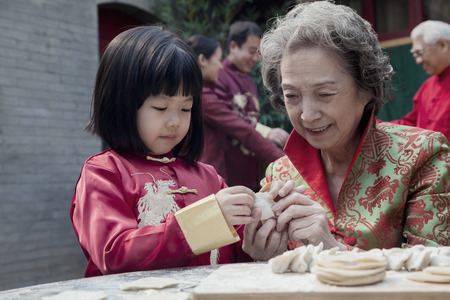 some under 18: Grandmother and granddaughter making dumplings in traditional clothing Stock Photo