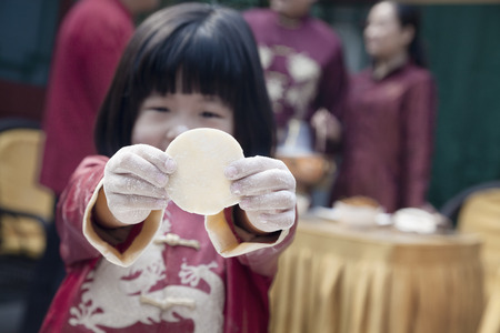 some under 18: Little girl showing dumpling wrapper in traditional clothing