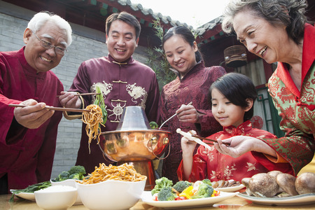 family eating: Family enjoying Chinese meal in traditional Chinese clothing Stock Photo