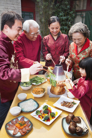 chinese people: Family enjoying Chinese meal in traditional Chinese clothing Stock Photo