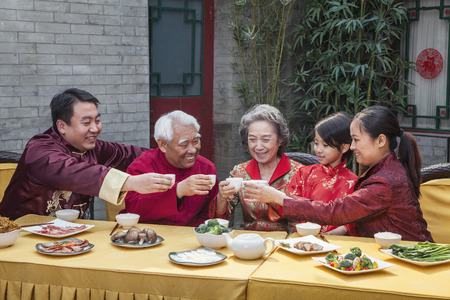 some under 18: Family with cups raised toasting over a Chinese meal