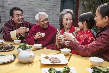 Family with cups raised toasting over a Chinese meal  photo