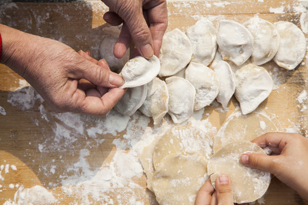 Senior woman and girl making dumplings, hands only