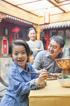 chinese women: Portrait of little girl eating dinner with her family Stock Photo