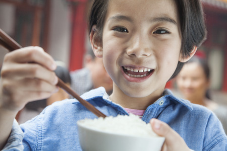 some under 18: Portrait of little girl eating rice Stock Photo
