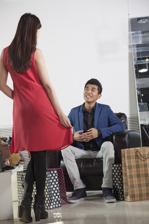 Young woman posing for man at fashion store photo