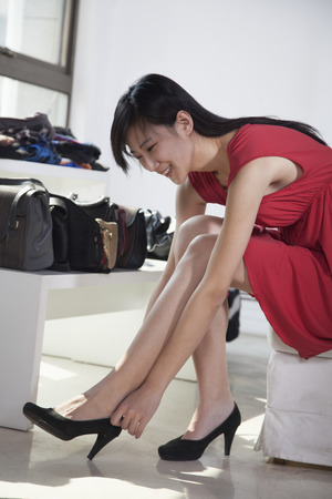 Woman trying on shoes at fashion store photo