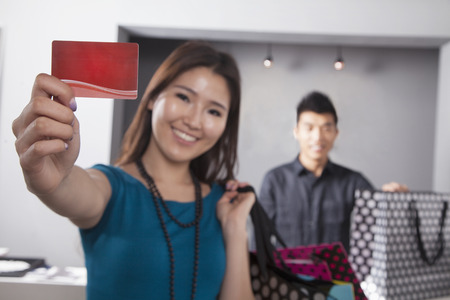 above 21: Young woman holding credit card at fashion store Stock Photo