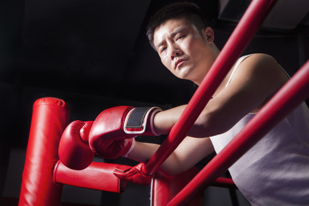 above 30: Portrait of male boxer resting his elbows on the ring side, low angle view Stock Photo