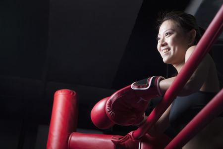 above 30: Smiling female boxer resting her elbows on the ring side, looking away, low angle view Stock Photo