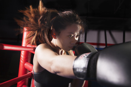 above 30: Close up of female boxer throwing a punch, hair in motion  Stock Photo