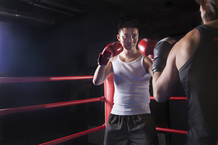 Over the shoulder view of two male boxers getting ready to box in the boxing ring in Beijing, China Imagens - 35993465