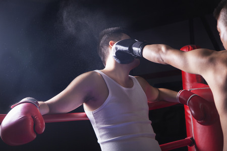 knockout: Over the shoulder view of male boxer throwing a knockout punch in the boxing ring