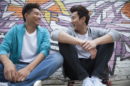 above 18: Two young men sitting on their skateboards and hanging out in front of a wall with graffiti Stock Photo