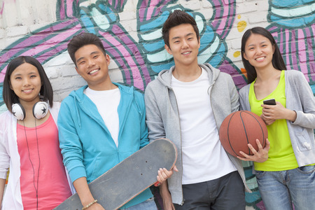 Portrait of four friends holding a skateboard and soccer ball hanging out in front of a wall covered in graffiti photo