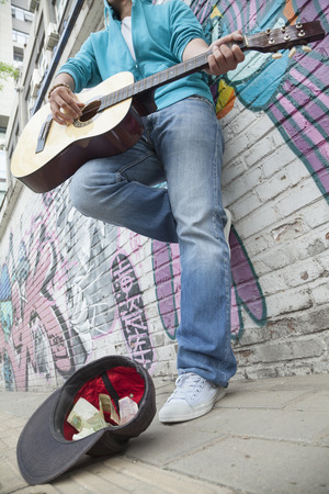 above 18: Young street musician playing guitar and busking for money in front of a wall with graffiti