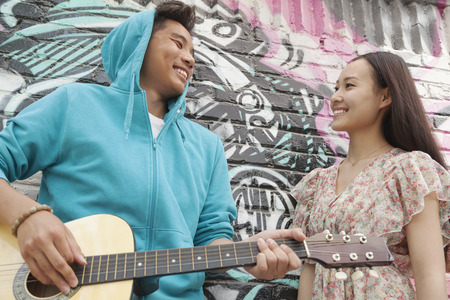 above 18: Young smiling street musician leaning on a wall with graffiti drawings, playing his guitar, and flirting with a young woman in a dress