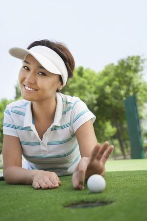 穴にボールをはじく準備ゴルフ コースに横たわる若い女性を笑顔