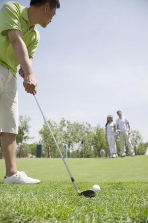 Young man hitting a ball on the golf course, man and woman in the background photo