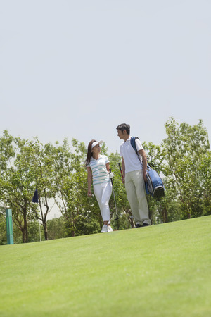 above 21: Female and male golfers talking and walking on the golf course