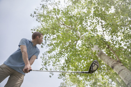 Low angle view of young man getting ready to hit the golf ball on the golf course photo