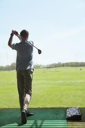 above 21: Rear view of young man hitting golf balls on the golf course, arms raised