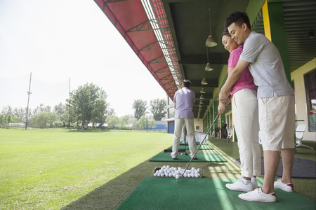 Young man teaching his girlfriend how to hit golf balls, arm around, side view photo