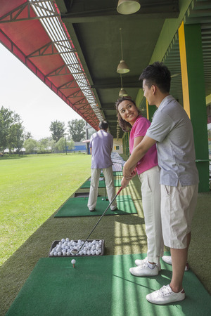 arm around: Young man teaching his girlfriend how to hit golf balls, arm around, side view