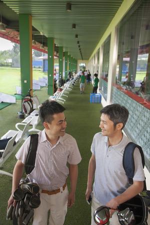 2 つの男性友人笑顔とゴルフ場を去る準備