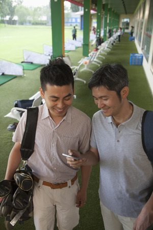 Two male friends smiling and getting ready to leave the golf course, looking down at phone photo