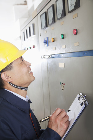 Smiling worker holding clipboard and checking controls in a gas plant, Beijing, China