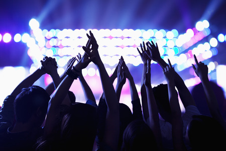 photography: Audience watching a rock show, hands in the air, rear view, stage lights Stock Photo
