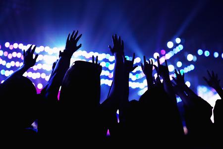 show of hands: Pubblico guardando uno spettacolo rock, le mani in aria, vista posteriore, luci di scena Archivio Fotografico
