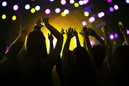 show hands: Audience watching a rock show, hands in the air, rear view, stage lights Stock Photo